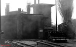 Through a drift of smoke from 99 2321, 99 2332 can just be made out standing next to the locked 2-road engine shed at Ostseebad Kühlungsborn West on 10th April 1991.